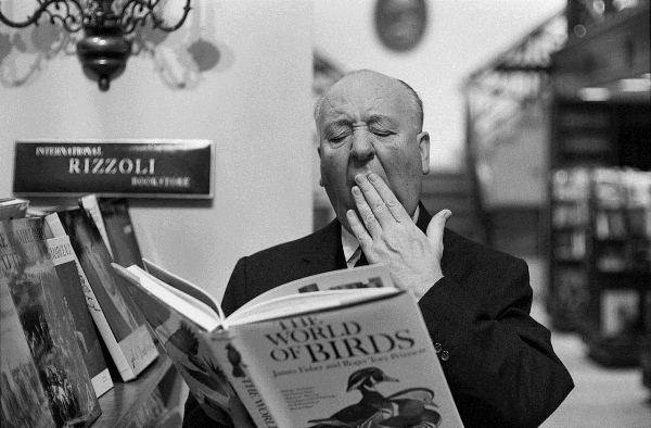 """Original Caption: 2/16/1965-New York, NY-Alfred Hitchcock won't reveal the subject of his next movie, but he's obviously bored with the former friends who starred in his scare-film """"The Birds.""""  The maestro of mayhem was caught in the """"ho hum"""" mood when he dropped in at the Rizzoli Bookstore on New York's Fifth Avenue, to check on the latest """"Ghoulology."""""""